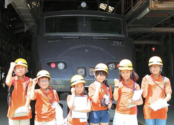 車両センターでは、点検中の電車の前で記念撮影。「たくさんの人の力で列車は動いているんだね!」